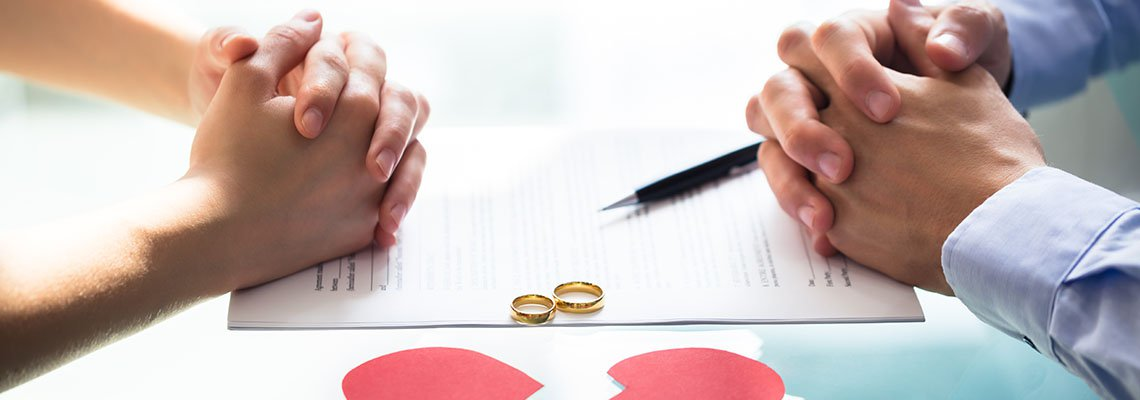 Couple resting hands on divorce document next to rings and a broken heart