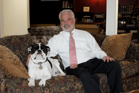 Attorney Doskocil Sitting on the couch with his arm around it dog