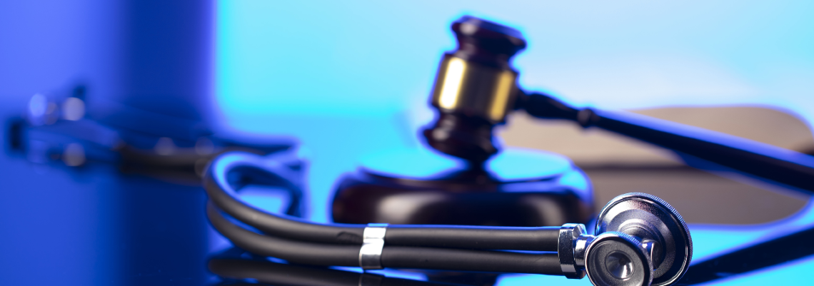 Gavel and Stethoscope Sitting on a Blue Table