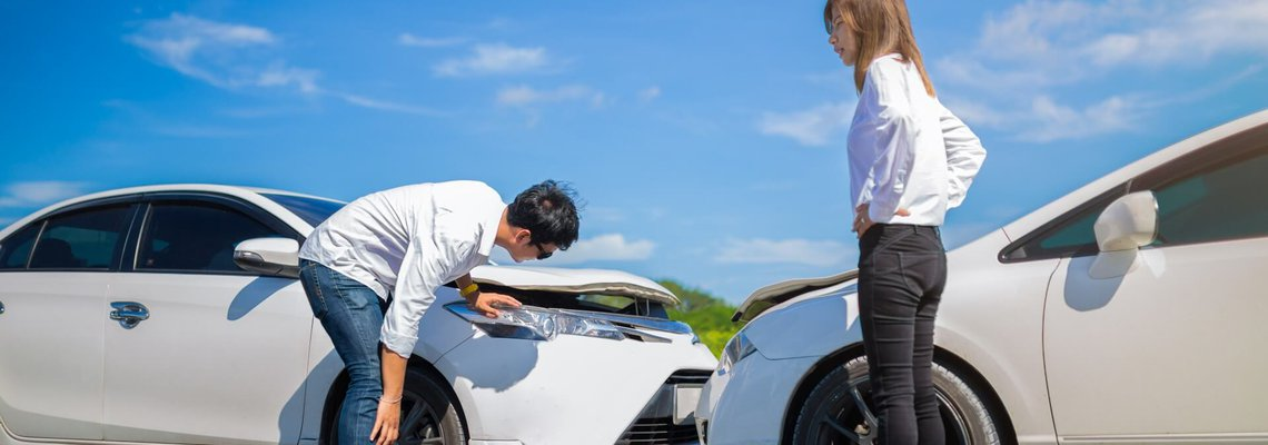 Two people inspecting damages to their cars after a collision