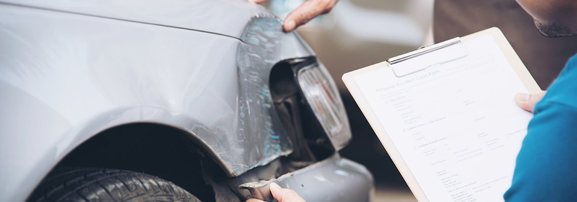 A person with a clipboard looks at a car