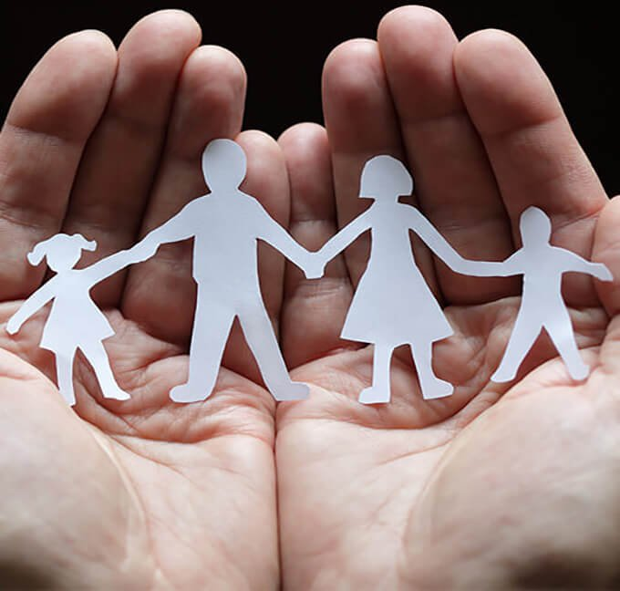 Hands Holding Paper Cut Out Family figures