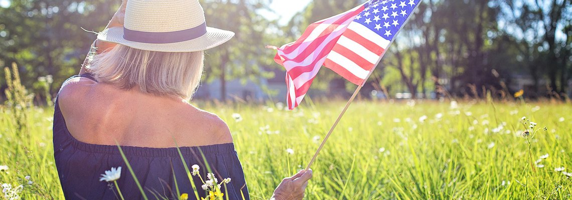 Woman Sitting on the Grass field and Wavering American Flag