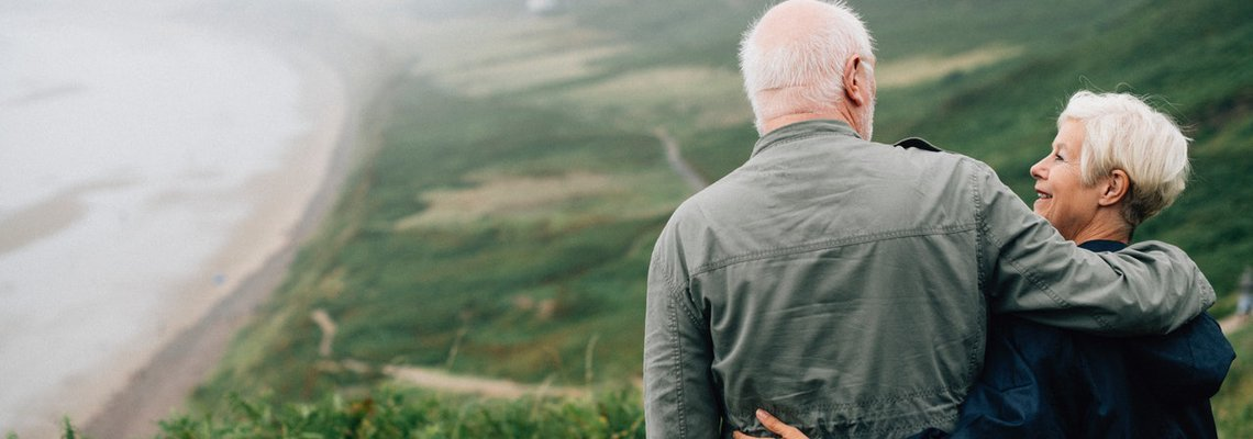 Elderly Couple Hugging on Top of The Hill