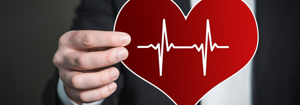 Man Holding a Heart Pulse Rate Icon