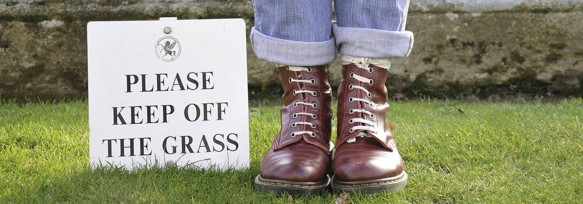 Woman Stepping on The Grass with A Sign Please Step out The Grass Next to Her Feet