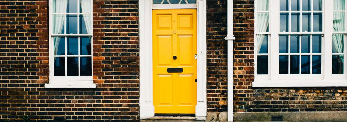 Yellow door on brick home