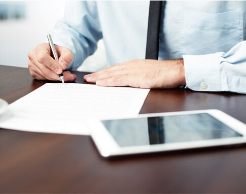 Man wearing tie writing on paper with tablet on desk