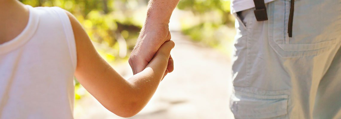 A child holding a parent's hand on a pathway
