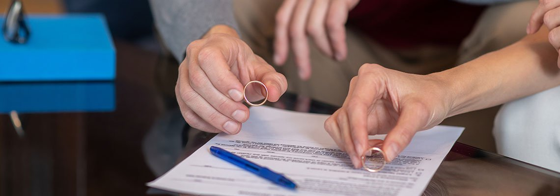 Couple signing documents and taking off wedding rings