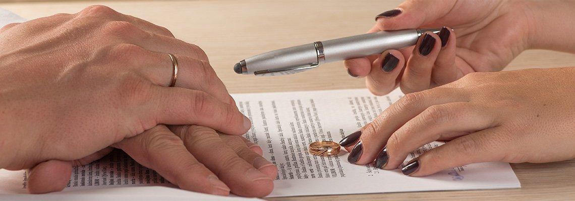 Man and woman signing divorce paperwork