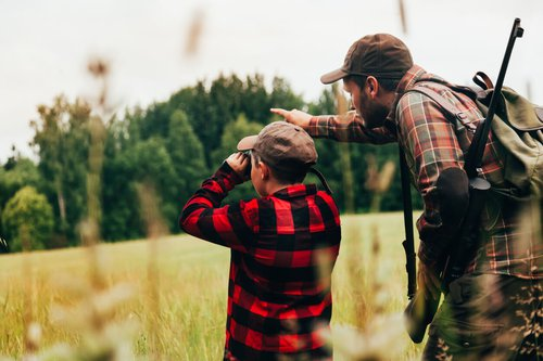 Father helping son hunt in the woods.jpg