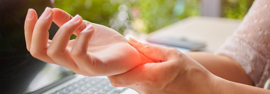 Woman holds her wrist in pain after typing