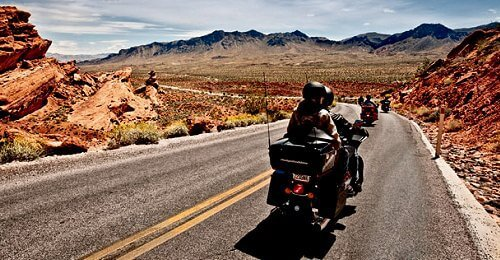 two people riding a motorcycle through mountainess desert