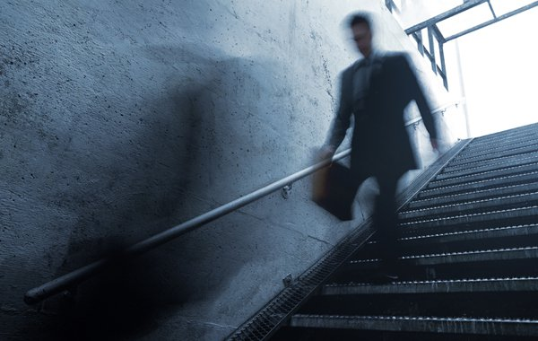 blurred man in suit walking down subway stairs