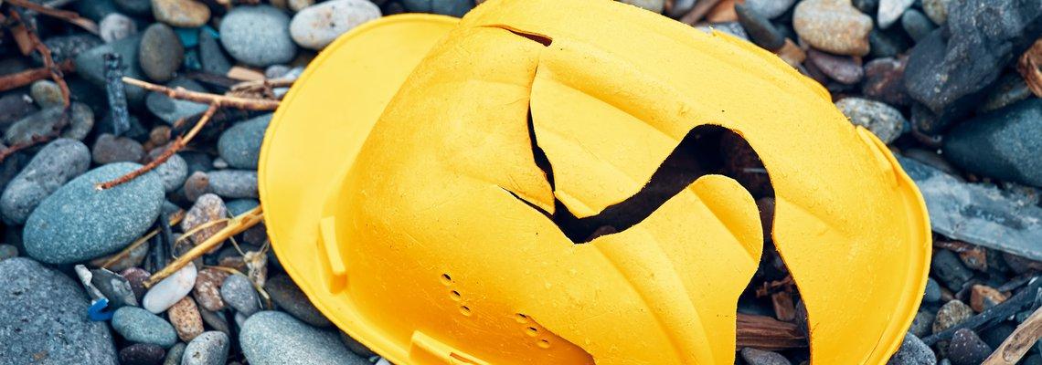 A cracked construction helmet lying on the ground.jpeg