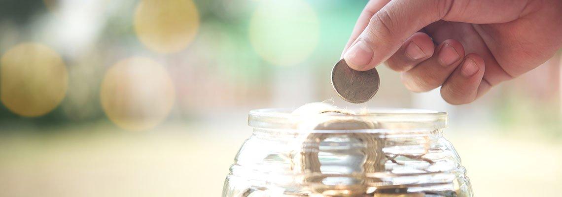 Hand putting money in jar