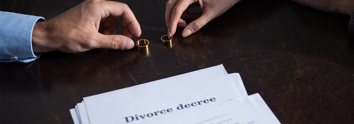 couple with rings and divorce documents