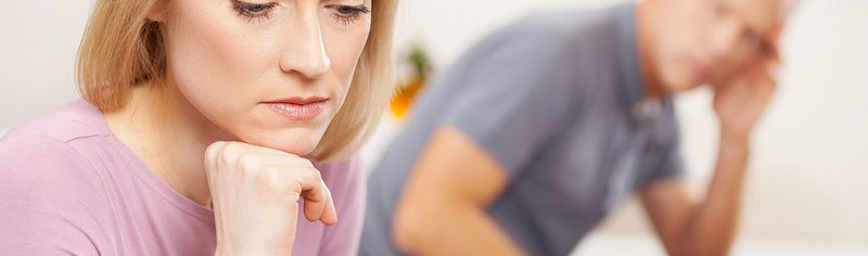 stressed woman looking down with man in background looking at her