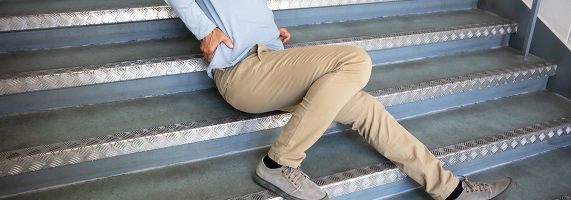Man gripping back after slip on stairs