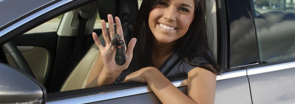 Young woman in car smiling and displaying keys