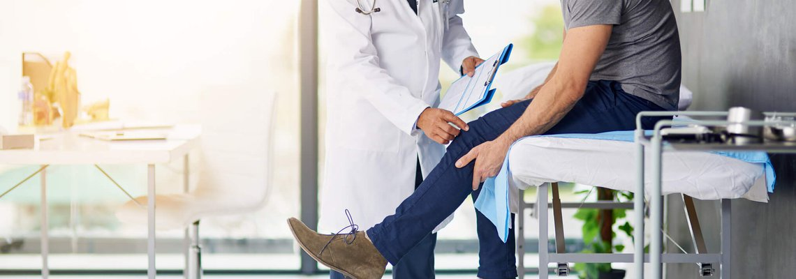 Man having knee examined by doctor