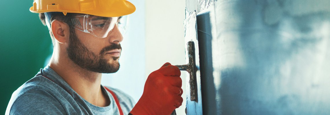 Male construction worker with hard hat smoothing the walls with a scraper