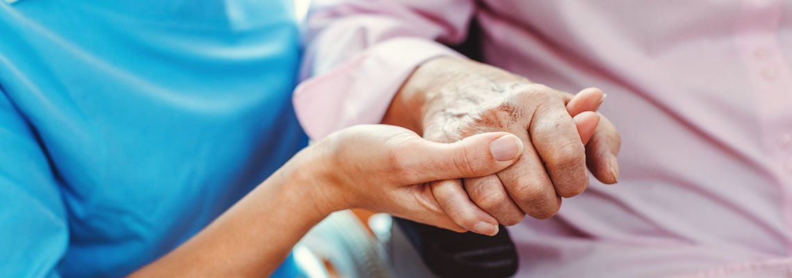 nursing home staff holding a patient's hand