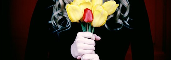 A person in black holding yellow and red tulips