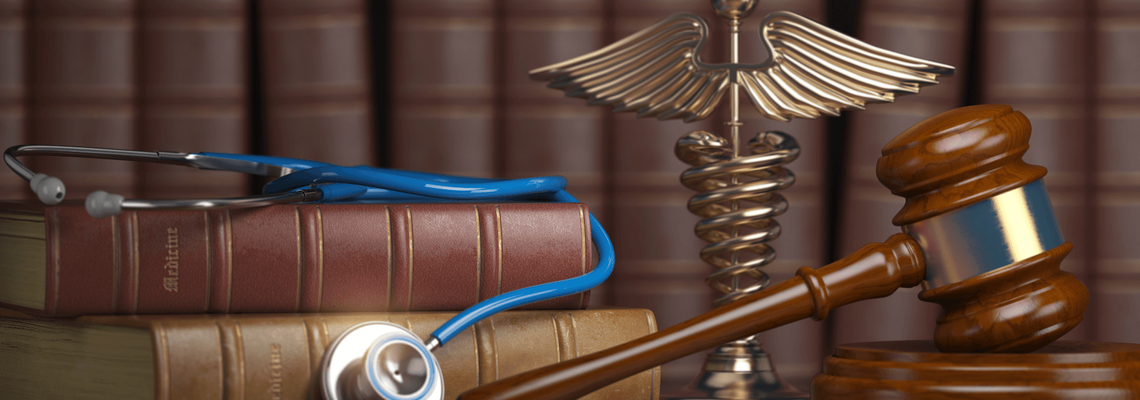 Stethoscope lying on a stack of books next to a gavel and a caduceus statue