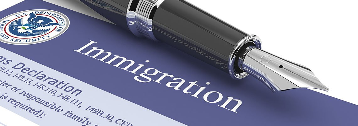 Immigration document with a pen resting on it