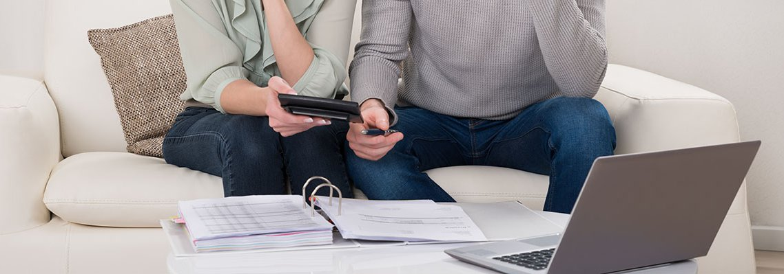 Man and woman sitting on couch looking at a binder, calculator, and computer