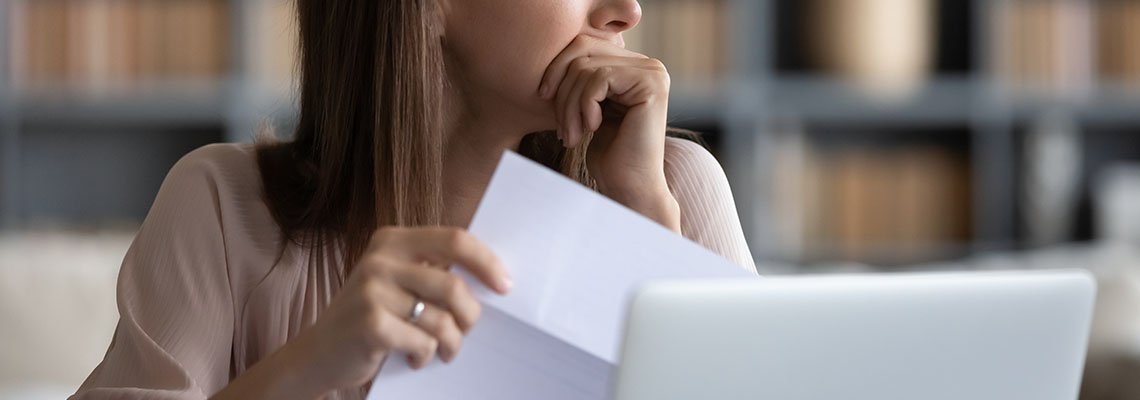 Woman looking pensive holding a paper
