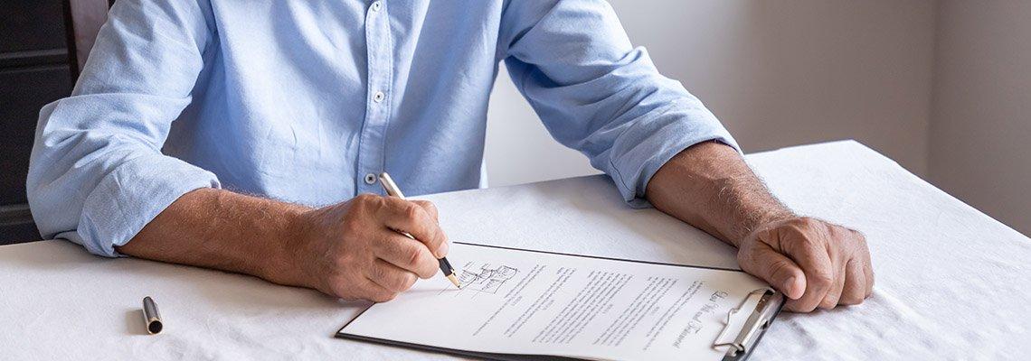 An older man signs a document