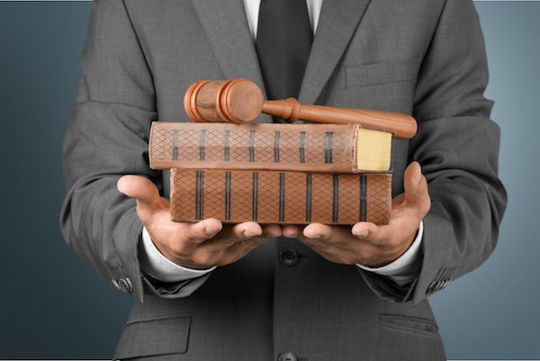 Man in gray suit holding books and gavel