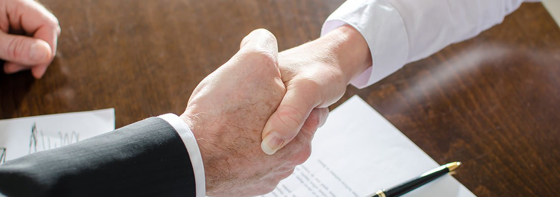 Two people shaking hands over an agreement