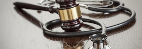 Stethoscope with gavel on wood table.jpg