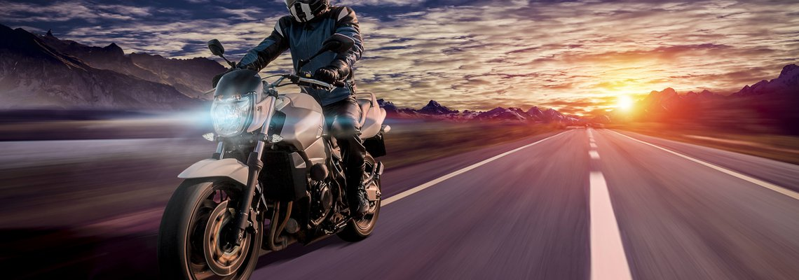 motorcyclist riding in the evening on a highway during sunset