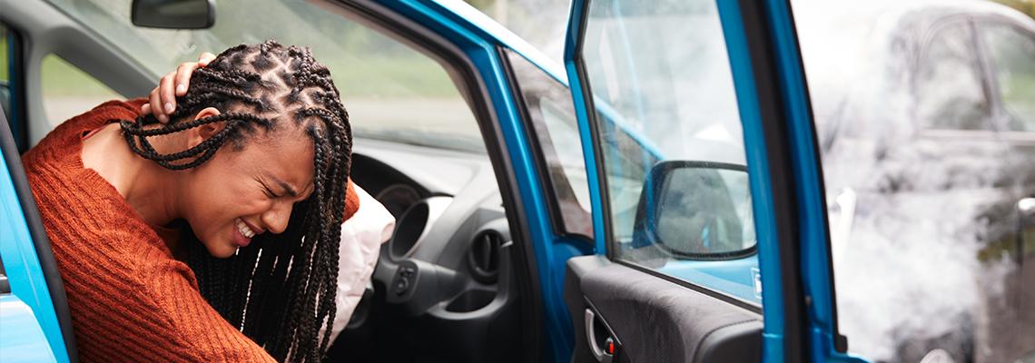 Female motorist holding her neck