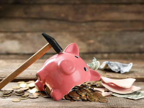 A hammer and a broken piggy bank with coins flowing out