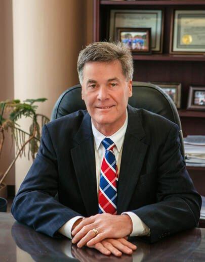 John Hoekstra in suit at desk