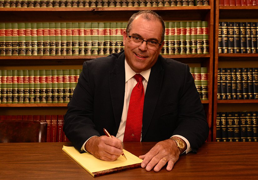 Attorney Richard Hyde writing on a legal notepad