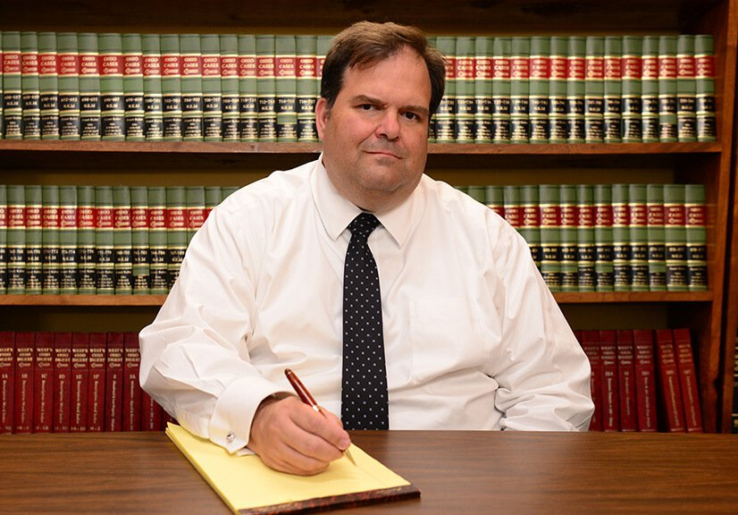 Attorney John Holcomb writing on a legal notepad