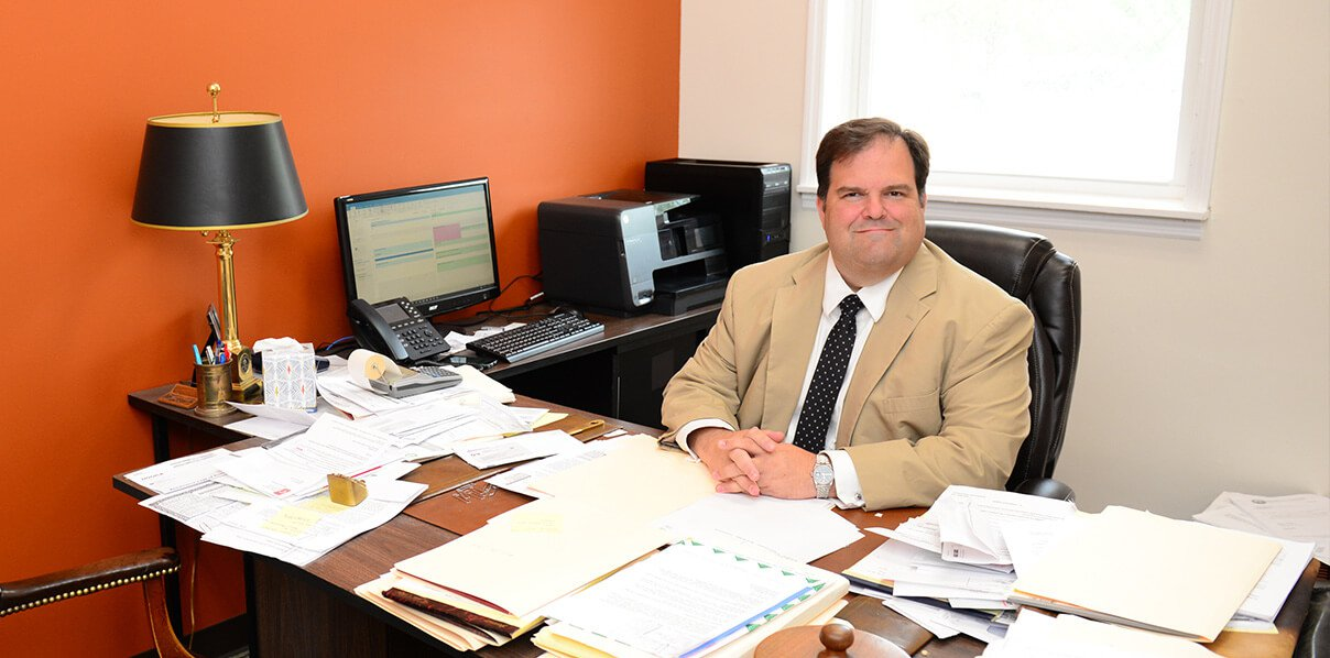 Attorney John Holcomb sitting at his desk with papers and folders all over his desk