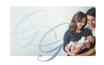 Woman holding infant and man standing close smiling down at the baby