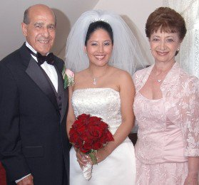 Woman in wedding dress smiling for picture with older man and woman on either side of her