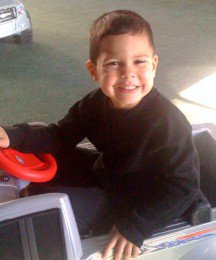 Young boy smiling in toy truck