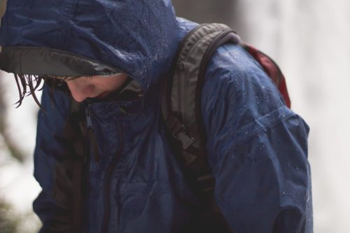 Person in raincoat with backpack on looking down