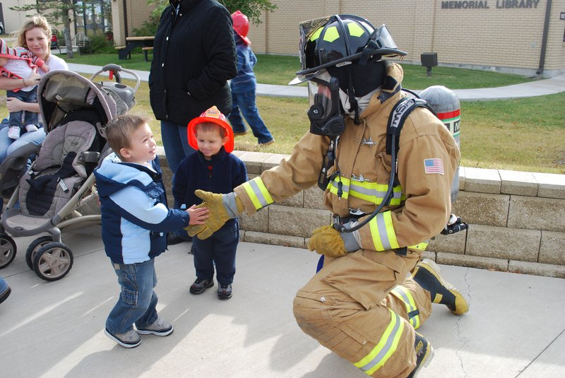 firefighter shaking hands with young boy