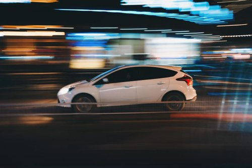car driving with blurred lights in the background
